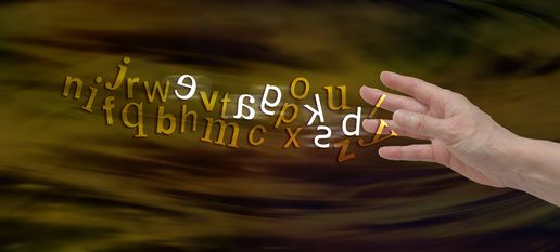 Understanding Dyslexia Website Banner - female hand with the alphabet flowing from fingers in gold with six letters flipped in white to symbolize dyslexia