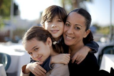 Niña con trenzas con su madre y hermano abrazándola